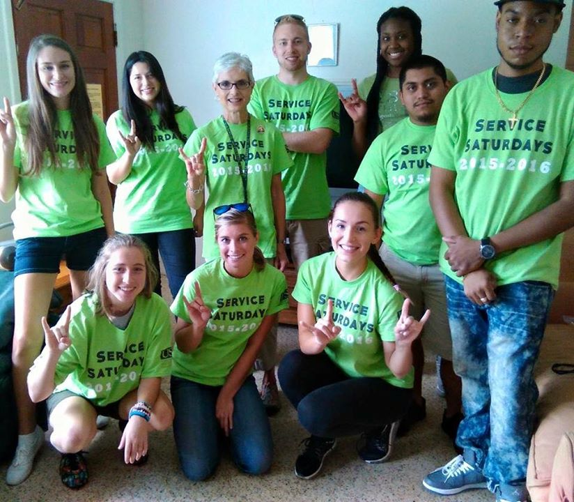 Dr. Sandra Stone surrounded by USFSM student volunteers.